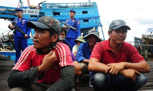 Petugas kepolisian mengawasi sejumlah nelayan Vietnam yang ditangkap karena mencuri ikan di Dermaga Direktorat Polisi Air (Dit Polair) Polda Kalbar, Kamis (3/3). Tim gabungan Polair Mabes Polri dan Dit Polair Polda Kalbar menangkap dua kapal Vietnam, yaitu KM Sinar 533 dan KM Sinar 288 berikut 25 Anak Buah Kapal (ABK) saat sedang mencuri ikan di perairan Pulau Sempadi, Kalbar, pada Selasa (1/3). ANTARA FOTO/Jessica Helena Wuysang/kye/16