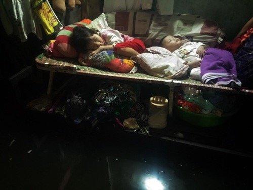 Bé gái 7 tuổi cùng em trai 6 tháng tuổi đang say giấc trên chiếc giường xếp trong phòng trọ ngập nước.