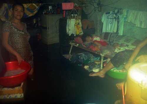 """Chị Nhàn giặt đồ trong nước ngập. Bên cạnh chị đứng là chiếc giường xếp nơi hai con nhỏ chị đang say giấc trong """"những ngày nước nổi ở Sài Gòn""""."""