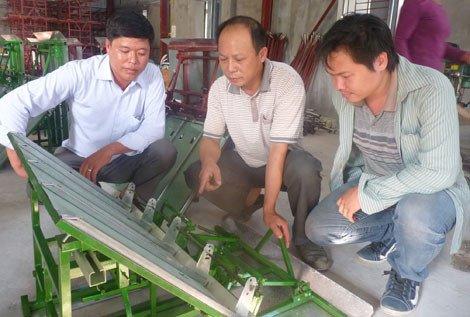 Anh Trần Đại Nghĩa đang giới thiệu nguyên lý hoạt động của máy cấy do anh chế tạo với khách tham quan.
